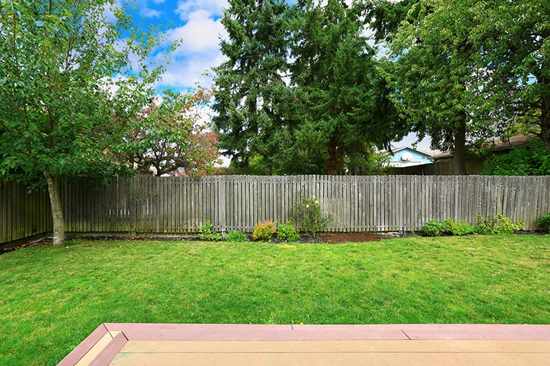 Countryside house backyard with old wooden fence.